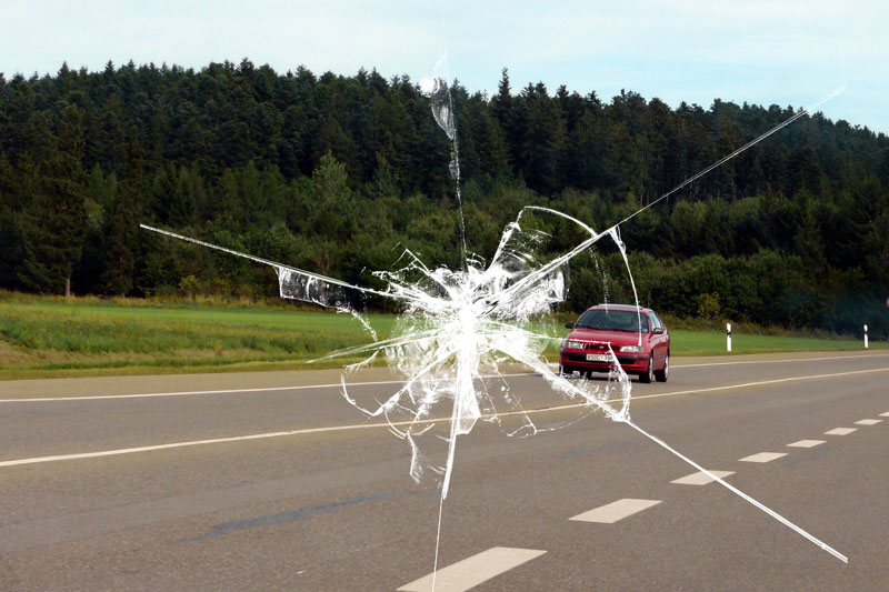 view of a highway through a chipped windshield