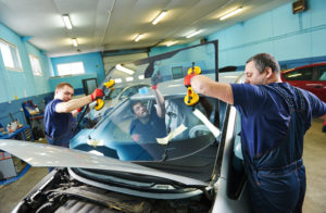 three workers replacing a windshield in an auto glass shop