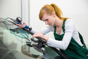 woman in car shop doing window chip repair on a vehicle