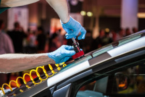 hands with blue gloves doing windshield chip repair on a car