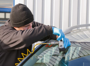 windshield crack repair being done by a beanie wearing mechanic