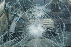 a severely broken car's windshield in need of auto glass replacement