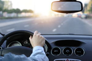 interior of a car with man driving on an empty freeway as the sun sets on the horizon