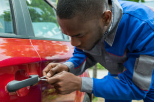 Young Male Mechanic Holding Lockpicker To Open Red Car Door