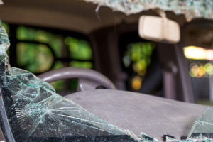 a car with a severely damaged and destroyed windshield