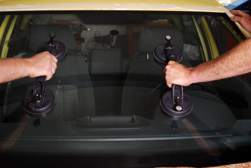 two hands on windshield holders as they perform mobile auto glass repair