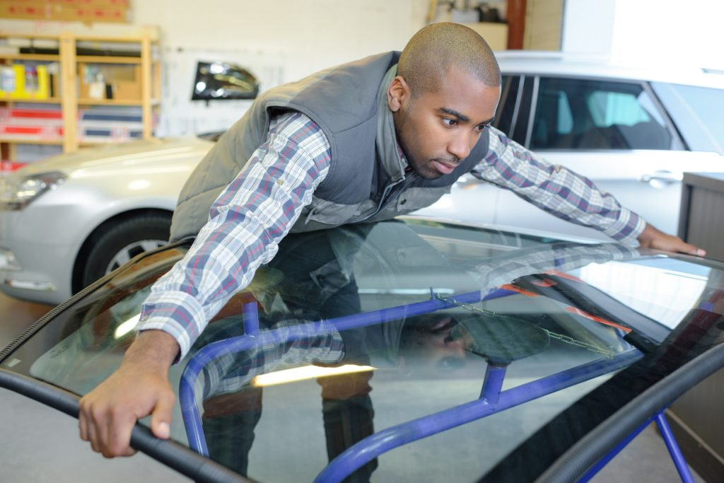 Worker holding car windshield
