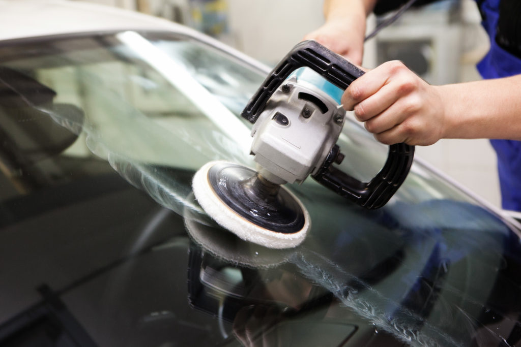 hand polishing a new windshield after auto glass repair
