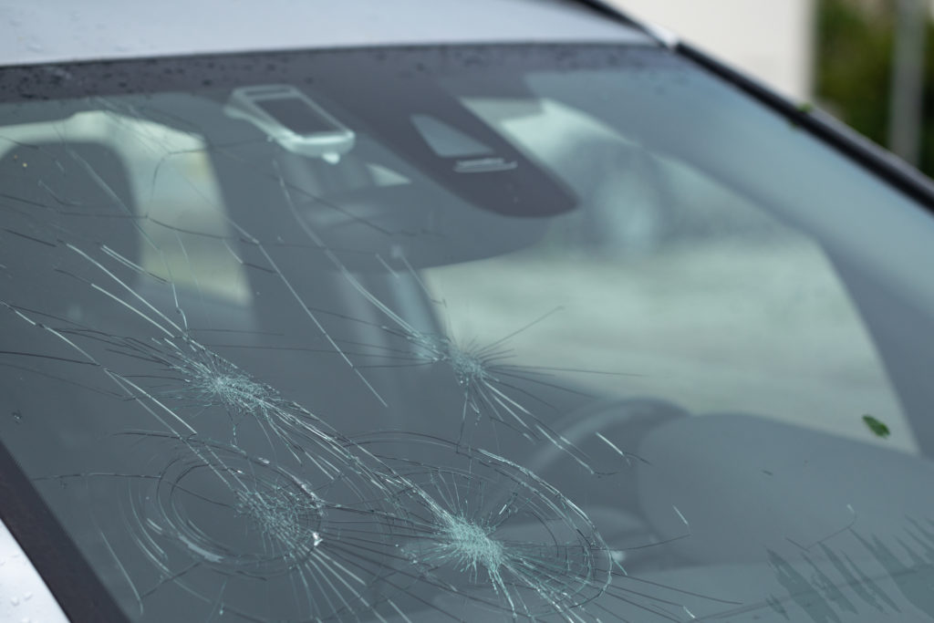 Severe damage to a windshield caused by a heavy hail storm