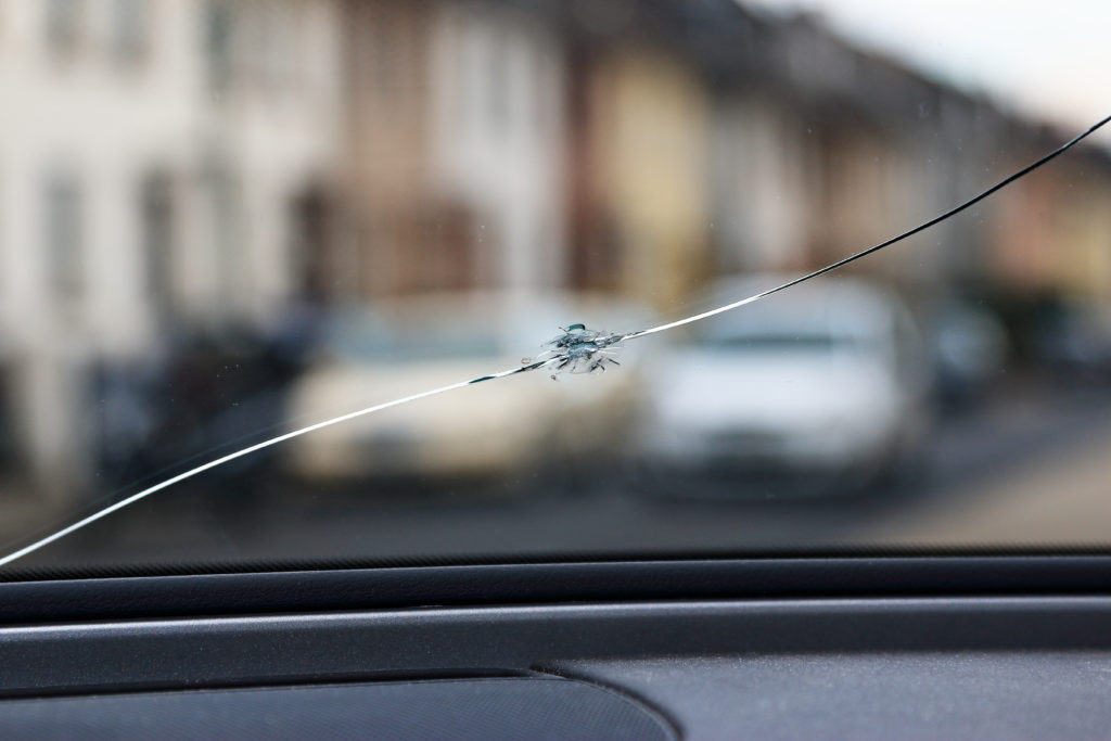 Long crack stretching across a vehicle's windshield.
